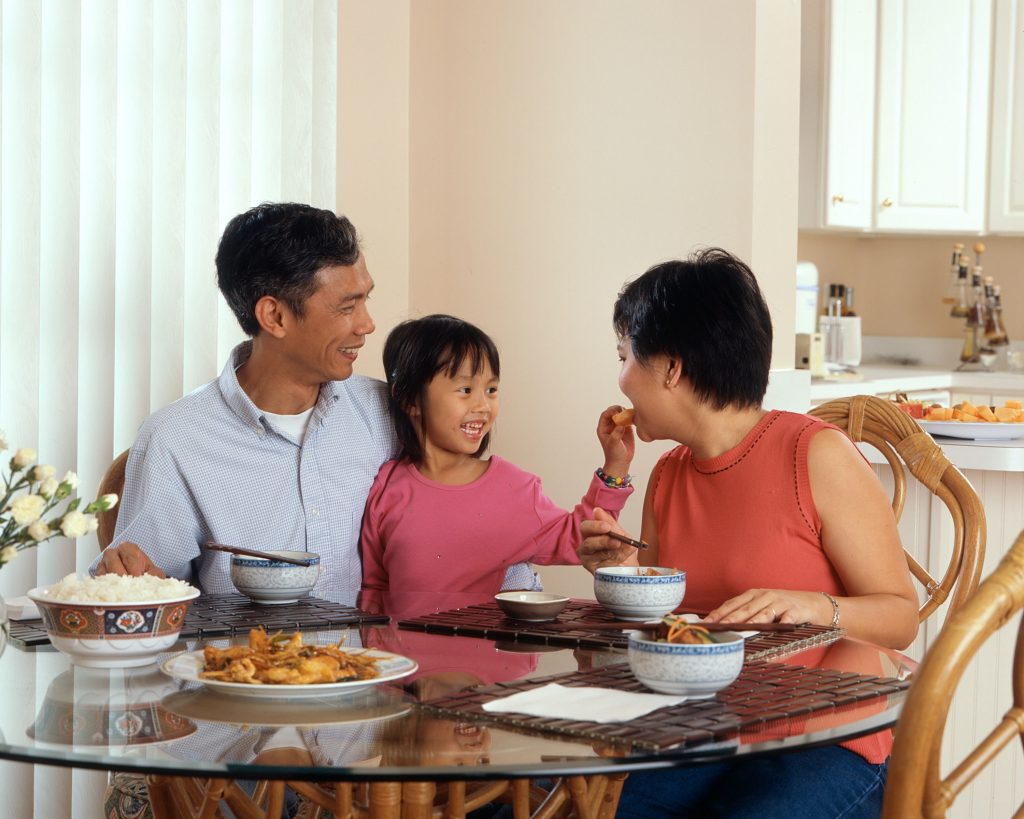 Family spending time together eating dinner in need of online therapy in the LA area