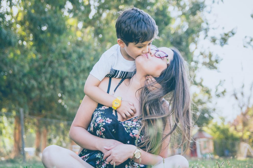 Mom getting affection from her son during pandemic in need of online therapy Los Angeles