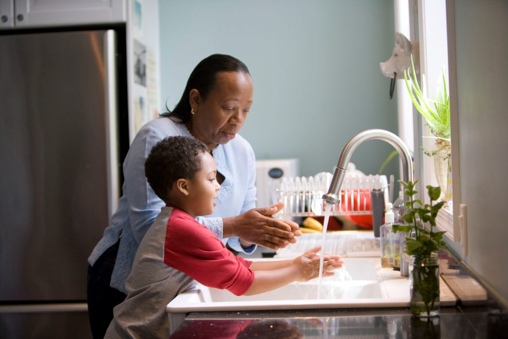 Grandmother and son doing dishes during the coronavirus pandemic feeling overwhelmed in need of online counseling in Los Angeles, Ca